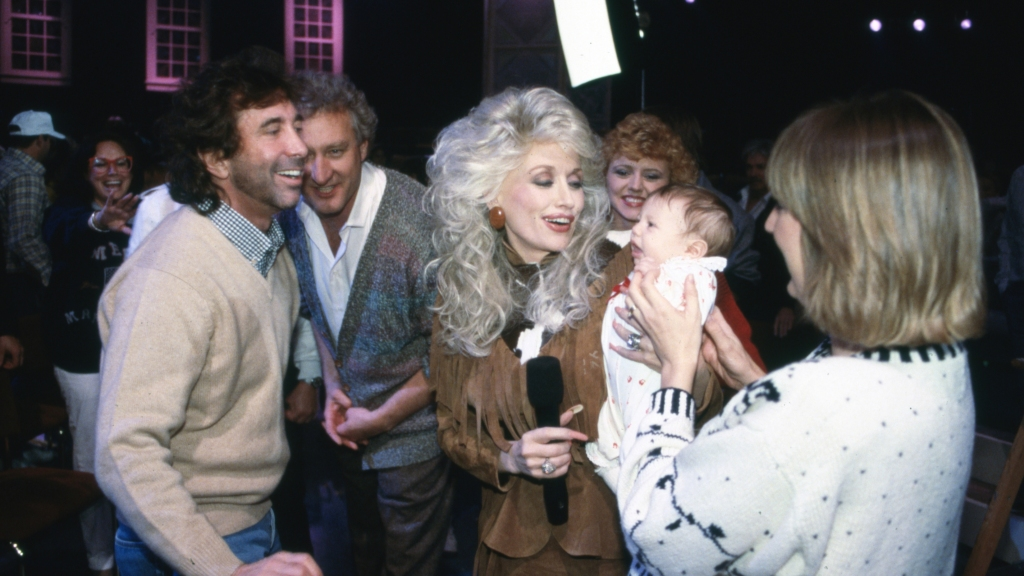 Dolly Parton being handed a baby