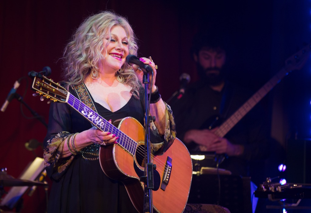 Stella Parton on stage with a guitar