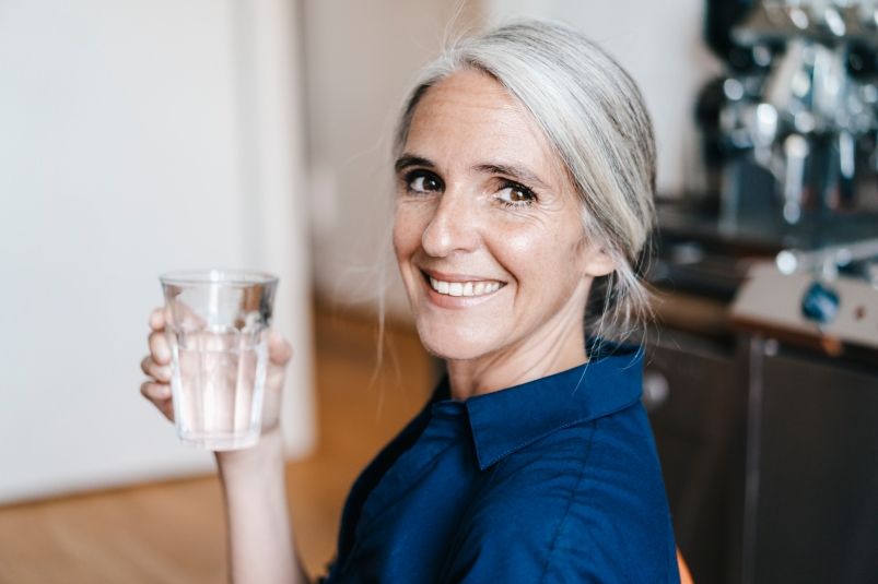 old woman with white hair tied back in a ponytail smiling with glass of water