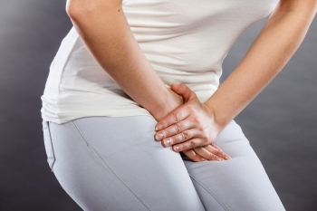 woman holding her crotch because she needs to go to the bathroom