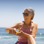 woman putting on sunscreen on the beach
