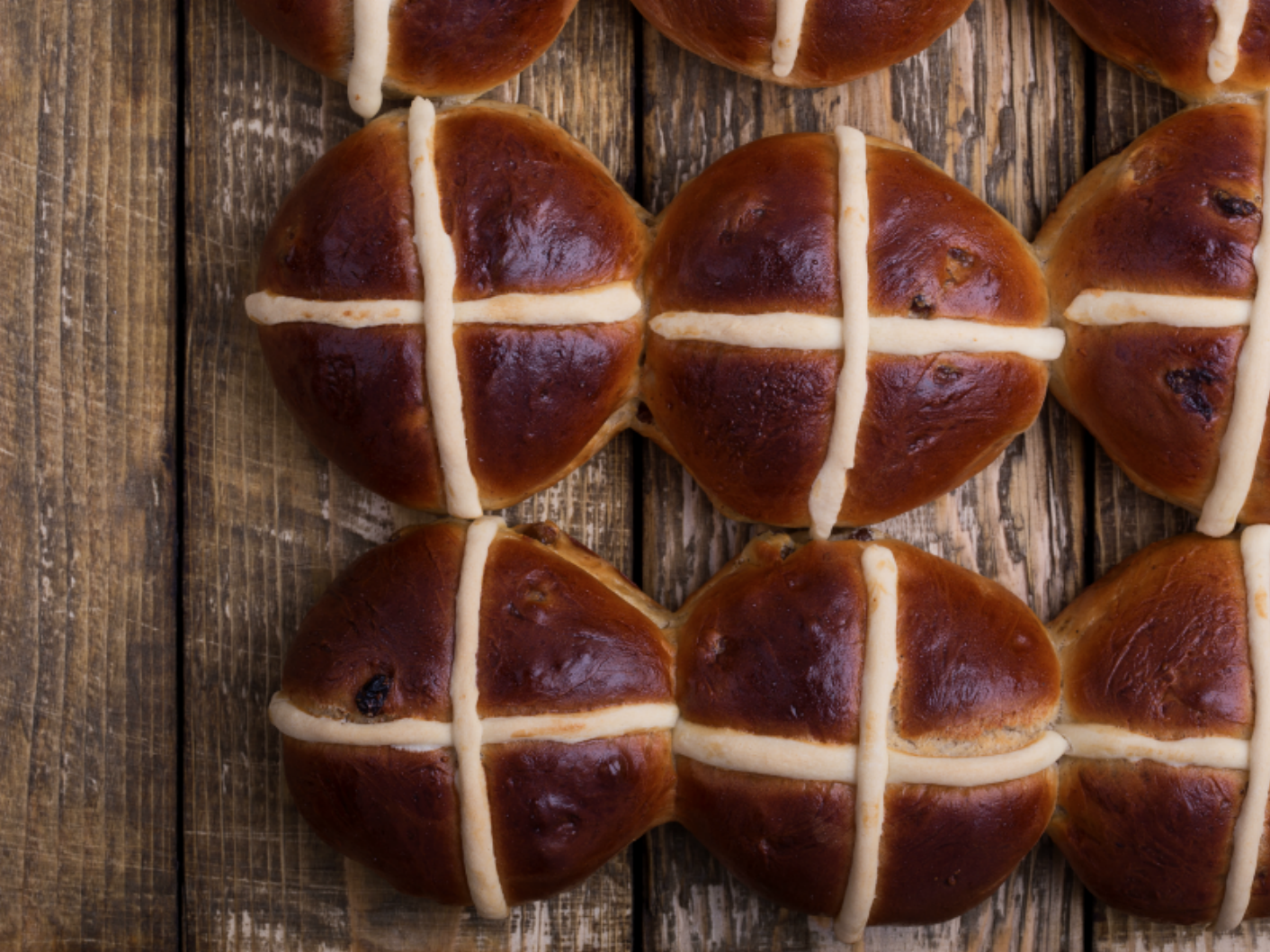 hot cross buns sitting on cutting board