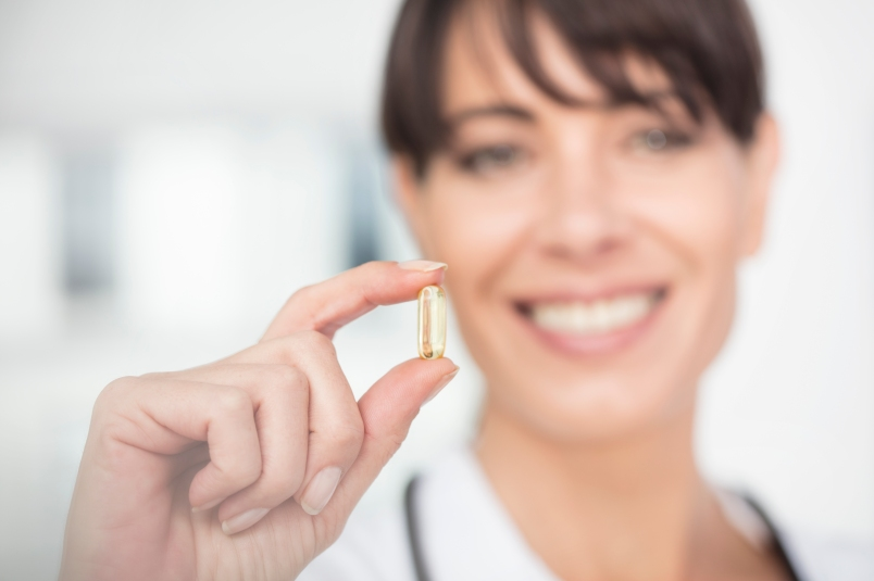 woman holding up a supplement and smiling