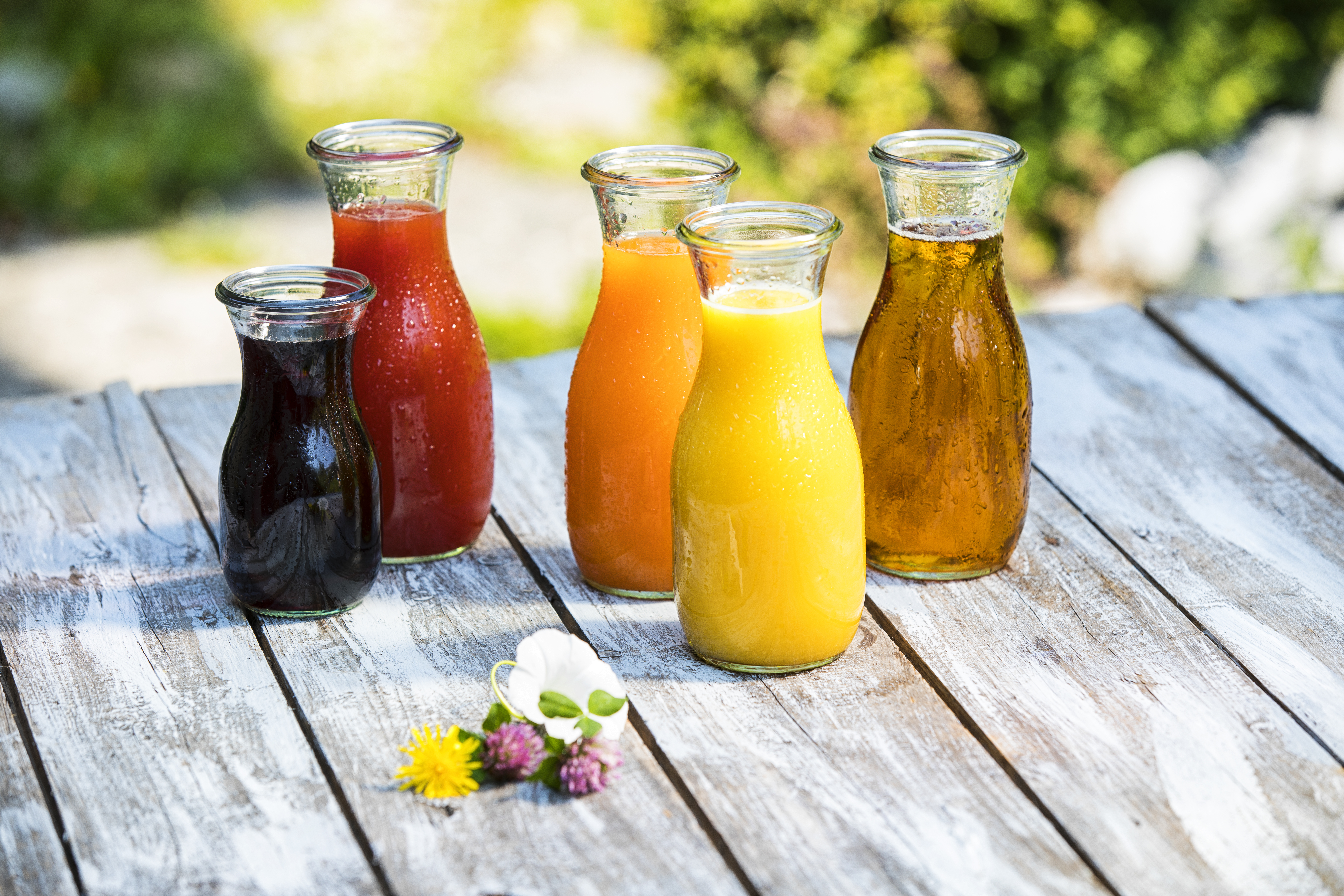 different fruit juices in glass jars