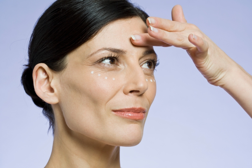 woman with hair pulled back touching a wrinkle on her forehead