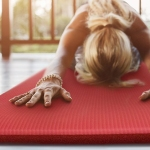 woman stretching out with her hands in front of her in a pose on a salmon -colored yoga mat