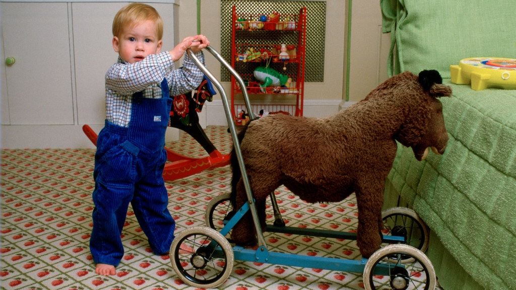 Prince Harry as a toddler with a toy horse