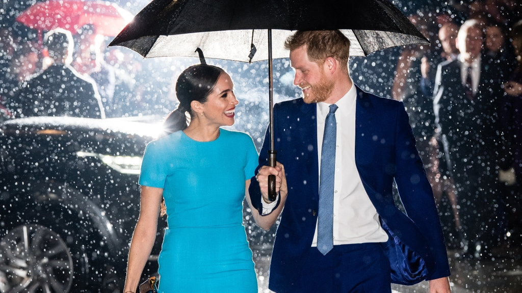 Prince Harry and Meghan smiling at each other under and umbrella