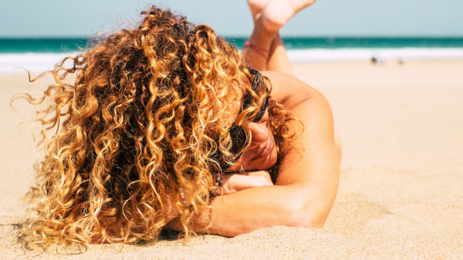 woman with curly hair on the beach