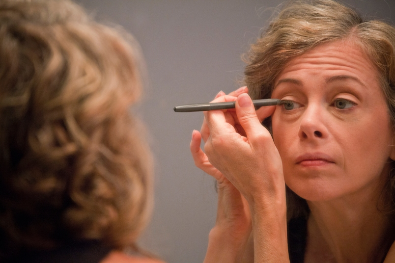 middle-aged woman applying eyeliner to one eyelid