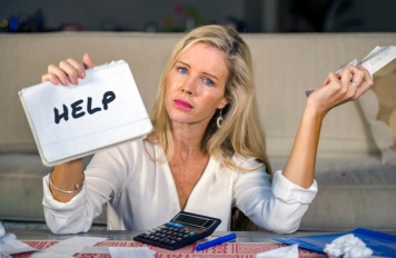 worried and stressed Caucasian 40s woman holding notepad calculating domestic expenses and taxes payments in budget problem and financial stress accounting with calculator