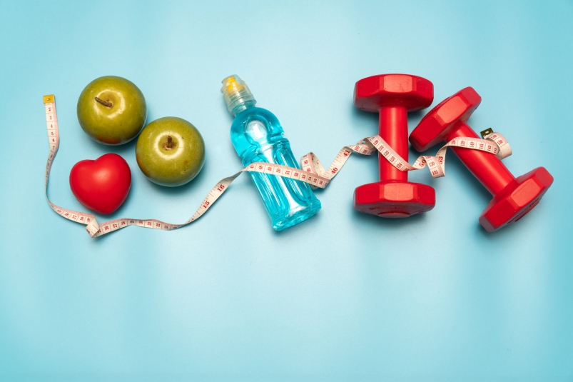 fruit, a water bottle, and weights on a blue background