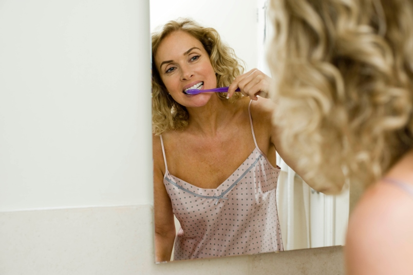 blonde woman brushing her teeth in a neglige