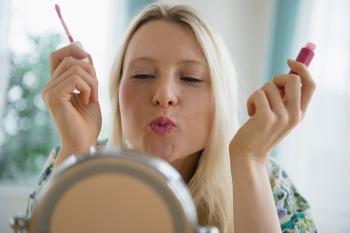 woman holding lip gloss and puckering her lips at a mirror