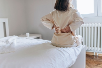 Woman feels back pain massaging aching muscles