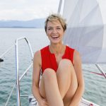 Mature woman sailing on Chiemsee lake, portrait, Bavaria, Germany