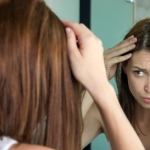 Woman looking at gray hairs in mirror