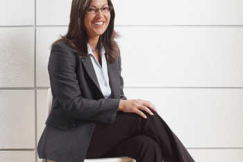 woman sitting in a pair of work pants and a blazer