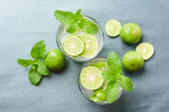 High Angle View Of Drinks With Limes And Mint Leaves On Table