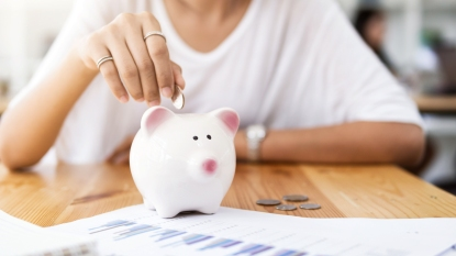Woman putting coin in piggy bank