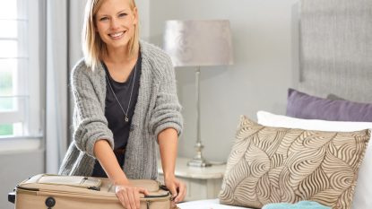 blonde woman organizing bedroom