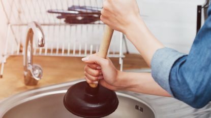 Cropped view of woman in denim shirt using plunger in sink