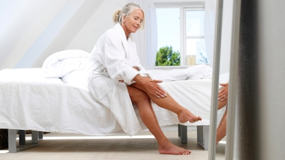 Mature woman sitting on bed in bathrobe, putting cream on her leg