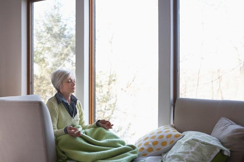 Senior woman meditating on sofa