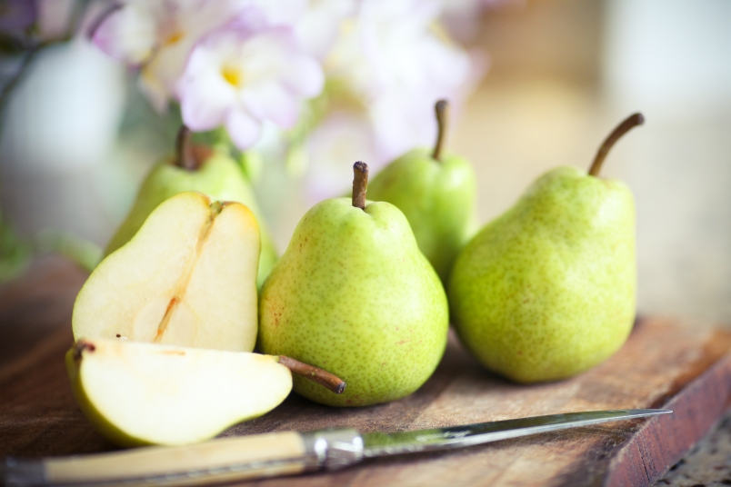 Green pears on wooden board with knife.