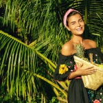 Happy young woman with a basket full of exotic fruits