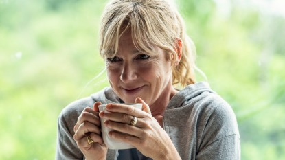 Smiling mature woman having coffee at home