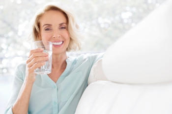 Mature woman smiling with glass of water.