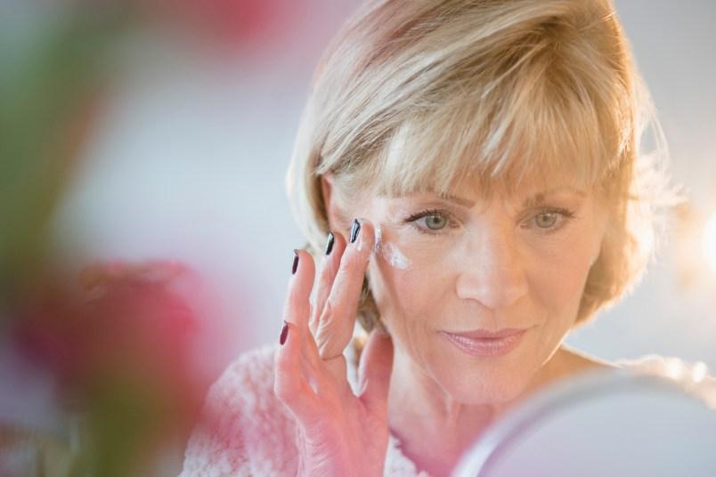 older caucasian woman applying eye cream