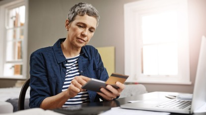 woman looking at credit card