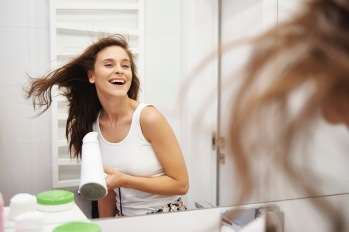 Mirror image of laughing woman blow-drying her hair in the bathroom