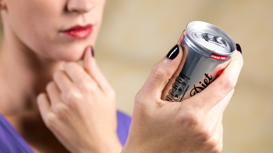 Woman looking at diet soda