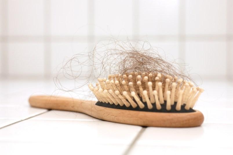 Hair loss in hairbrush on white tiles
