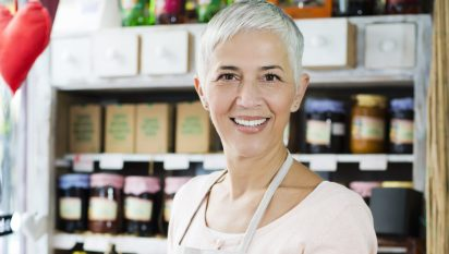 Mature woman holding homemade jam and juice at shop