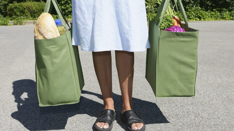 Woman with reusable grocery bag in each hand
