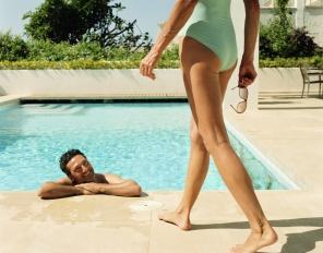 Woman standing by man smiling in swimming pool