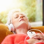 older woman relaxing with music on sofa