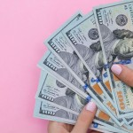 Woman holding $100 bills