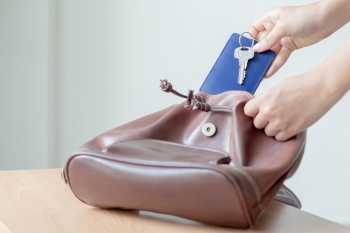 Cropped Hands Of Woman Putting Keys Into Purse On Table