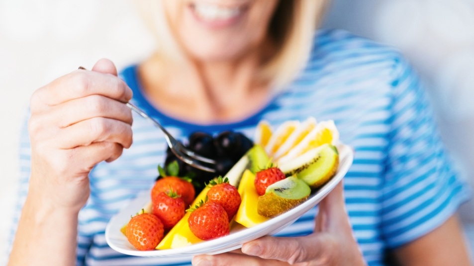 Woman eating plate of fruit