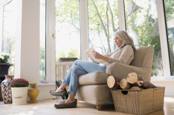 Senior woman reading in armchair