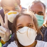 family outdoors wearing face masks taking selfie