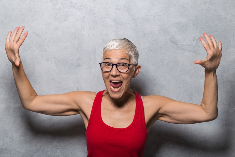 woman with gray hair and toned arms flexing