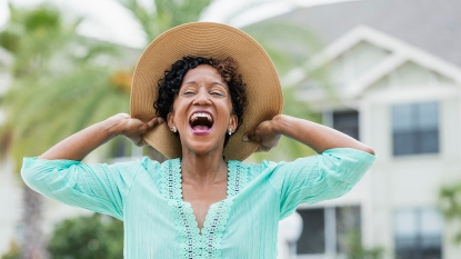 Black woman wearing hat and smiling