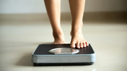 Woman's feet stepping onto a scale
