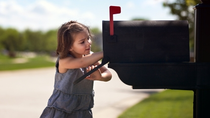 Little girl checking mail box